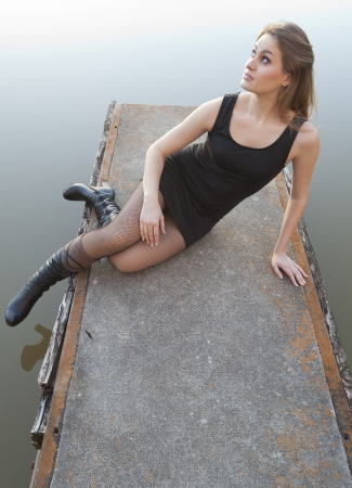 An attractive young woman relaxing on a dock