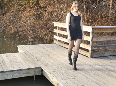 A beautiful young woman strutting on a wooden dock Stock Photo