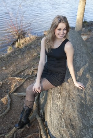 A beautiful young woman relaxing on a rock by a lake and looking over her shoulder smiling Stock Photo - 18154574