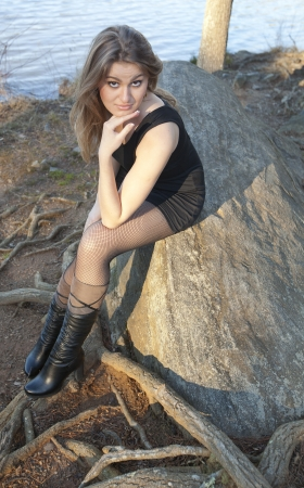 A beautiful young woman posing on a rock by a lake Imagens