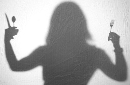 A silhouette of a woman holding silverware Stok Fotoğraf
