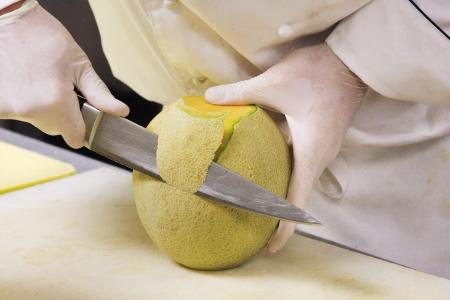 prep: A prep cook slicing a cantaloupe