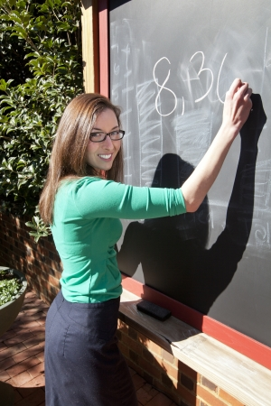 instructing: Pretty woman writing on an outdoor chalkboard