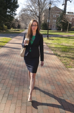 A young business woman walking with a coffee drink