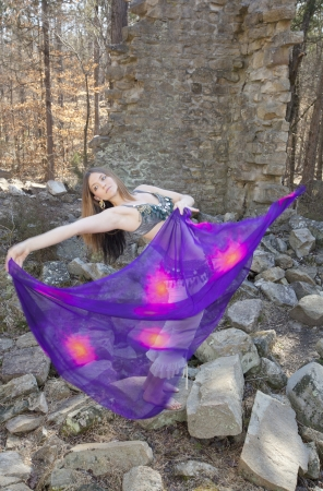 A young woman performing a belly dance with a colorful veil  photo