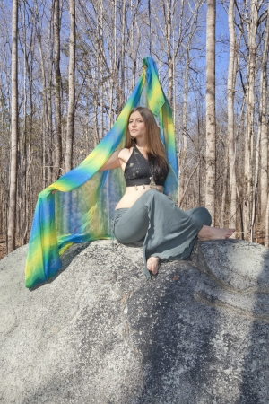 A mysterious young belly dancer extending  a colorful veil while sitting on a rock  photo