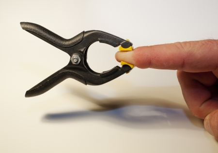 A clamp clipped tightly onto an index finger  Stock Photo - 18765661
