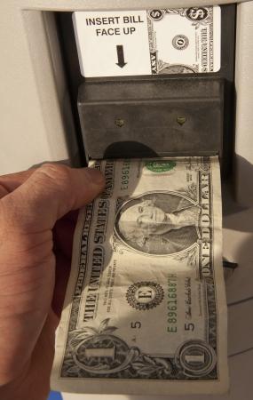 Feeding a dollar bill into a vending machine