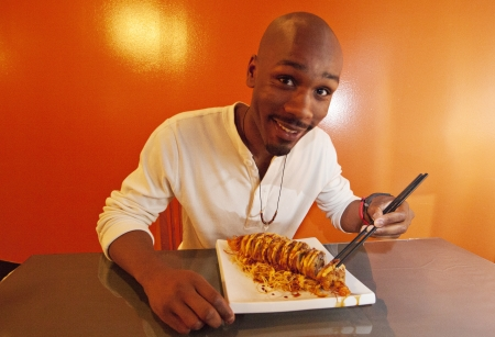 Young African American man eating sushi Stock Photo
