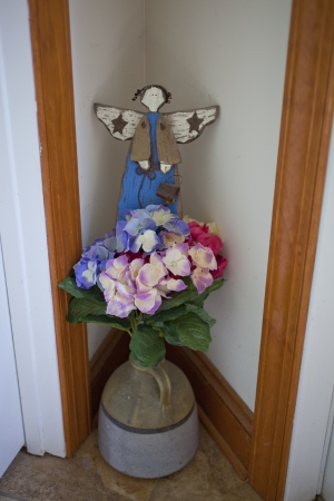 A decorative display angel, flowers, and an old whiskey jug Stock Photo - 19622523