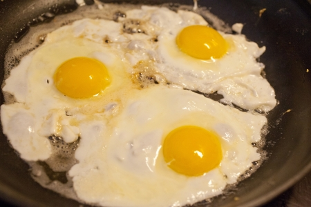 Eggs cooking in a frying pan  Stock Photo