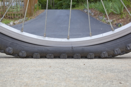 Closeup on a flat bicycle tire Imagens