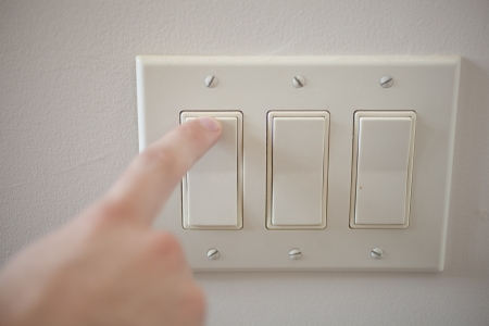 A finger switching off a light switch. Stock Photo - 20163969