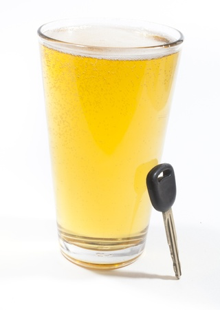 A pint of beer and a key to a vehicle isolated against a white background photo