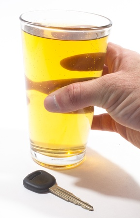A pint of beer and a key to a vehicle isolated against a white background