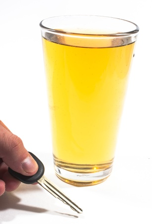 drink responsibly: A pint of beer and a key to a vehicle isolated against a white background