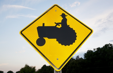 tractor warning sign: A tractor crossing road sign picturing on a rural road.