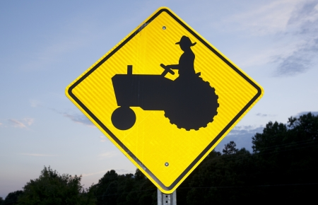 tractor warning: A tractor crossing road sign picturing on a rural road.
