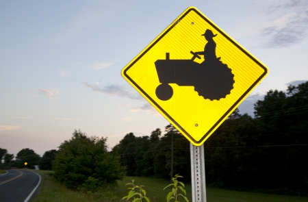A tractor crossing road sign picturing on a rural road.