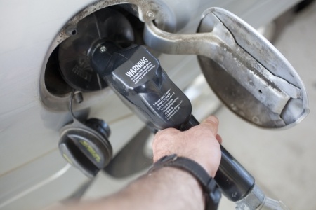 A gas pump inserted into a vehicle fuel tank opening Stock Photo - 20432486