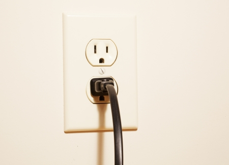 A plug connected to an electrical outlet Stock Photo - 20494241