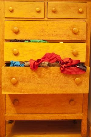 d�bord�: Une commode en bois avec un tiroir d�bordant de v�tements Banque d'images