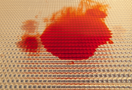 An abstract of bright red splattered liquid spreading out against a metallic background