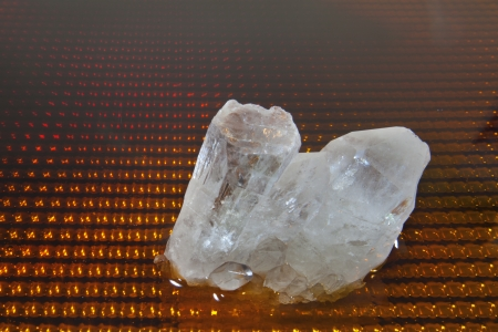 A quartz crystal against a colorful background. Stock Photo - 20692184