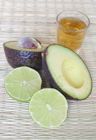 An avocado and lime cut in half on a straw mat with a shot of tequila. Stock Photo
