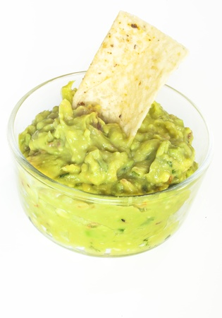 avacado: A bowl filled with guacamole and a tortilla chip
