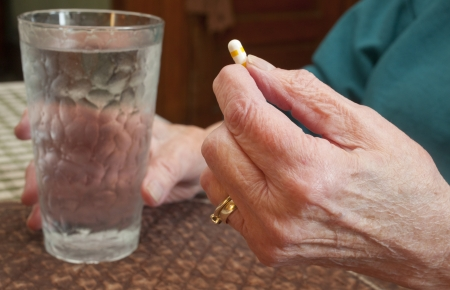 care providers: An elderly woman about to take a pill