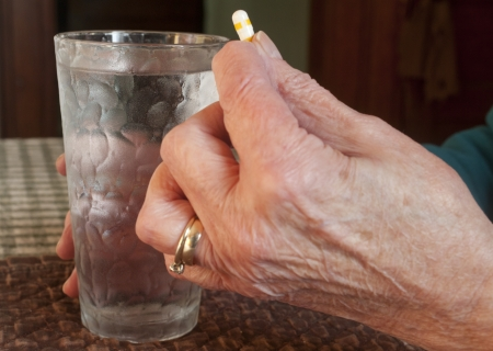 An elderly woman about to take a pill. photo
