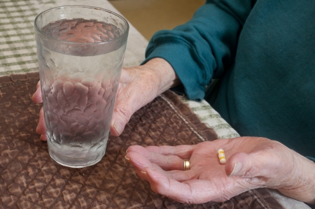 An elderly woman about to take a pill.