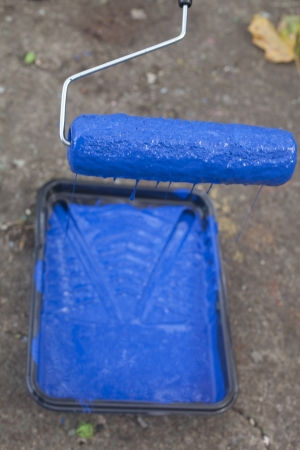 A paint roller dripping blue paint into a tray Stock Photo - 23776849