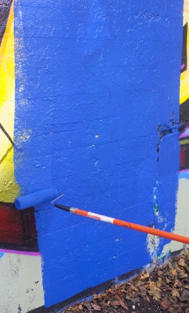 Painting over graffiti on a wall with a paint roller Stock Photo - 23776851