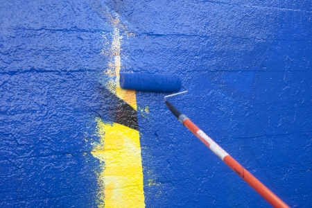 Painting over graffiti on a wall with a paint roller Stock Photo - 23776891
