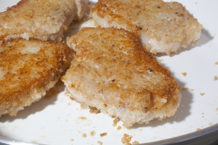Browning breaded pork chops on a ceramic skillet. Stock Photo