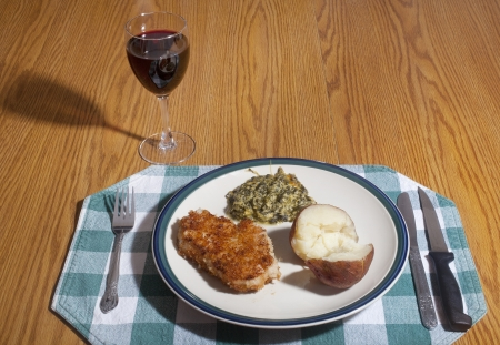 A dinner plate of breaded Pork chop, baked potato and spinach pie, on a table with a glass of red wine. photo