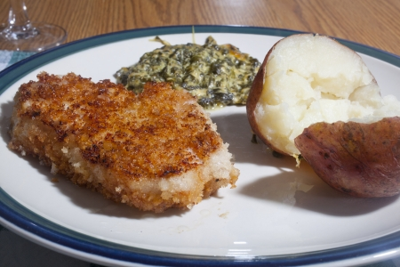 breaded pork chop: A breaded pork chop with a baked potato and spinach pie side