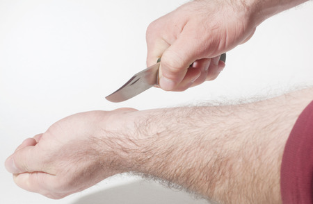 rock bottom: Suicide attempt by slitting the wrist with a knife  Stock Photo