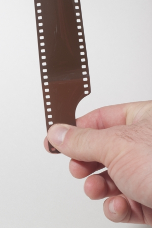 A hand pulling a 35mm film strip  photo