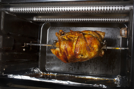 A chicken cooking on a horizontal rotisserie