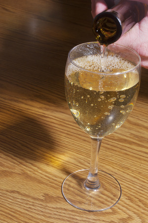 bottleneck: Pouring a glass of white wine