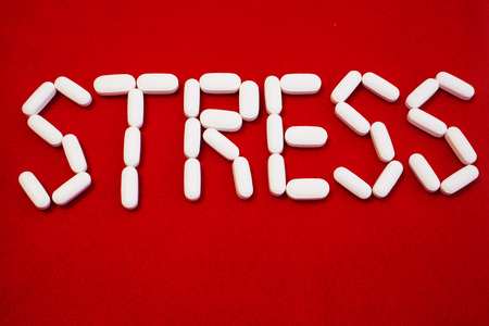 The word stress spelled out with white pills against a red background  Stock Photo