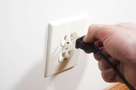wall socket: A hand putting a two prong plug into a wall socket