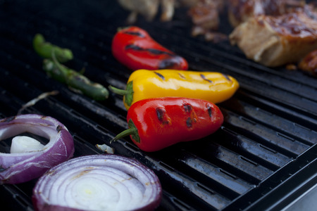 charred: Peppers and onions and Barbecue Pork cooking on a grill  Stock Photo