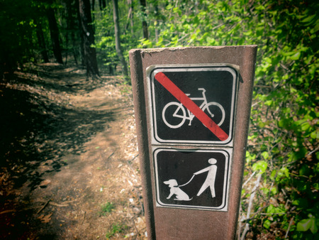 A filtered photo of a sign post with symbols for biking not allowed and dog walking on leash allowed. photo