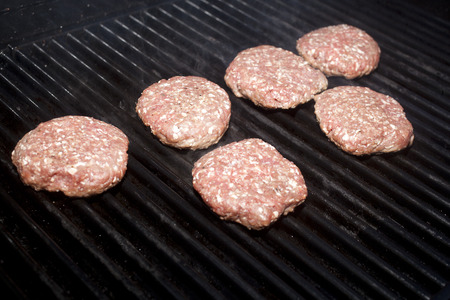 Hamburger patties cooking on a grill