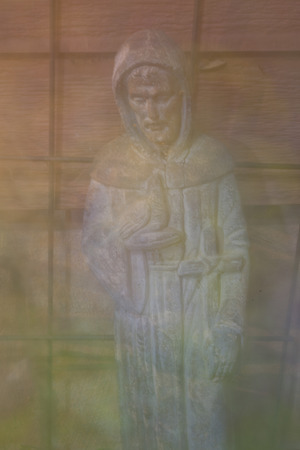 A digitally altered background photo of a Saint Francis of Assisi garden statue.