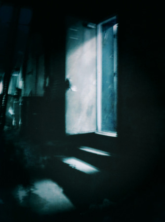 A filtered abstract scene of a dark alleyway at night with light shining through an open doorway photo